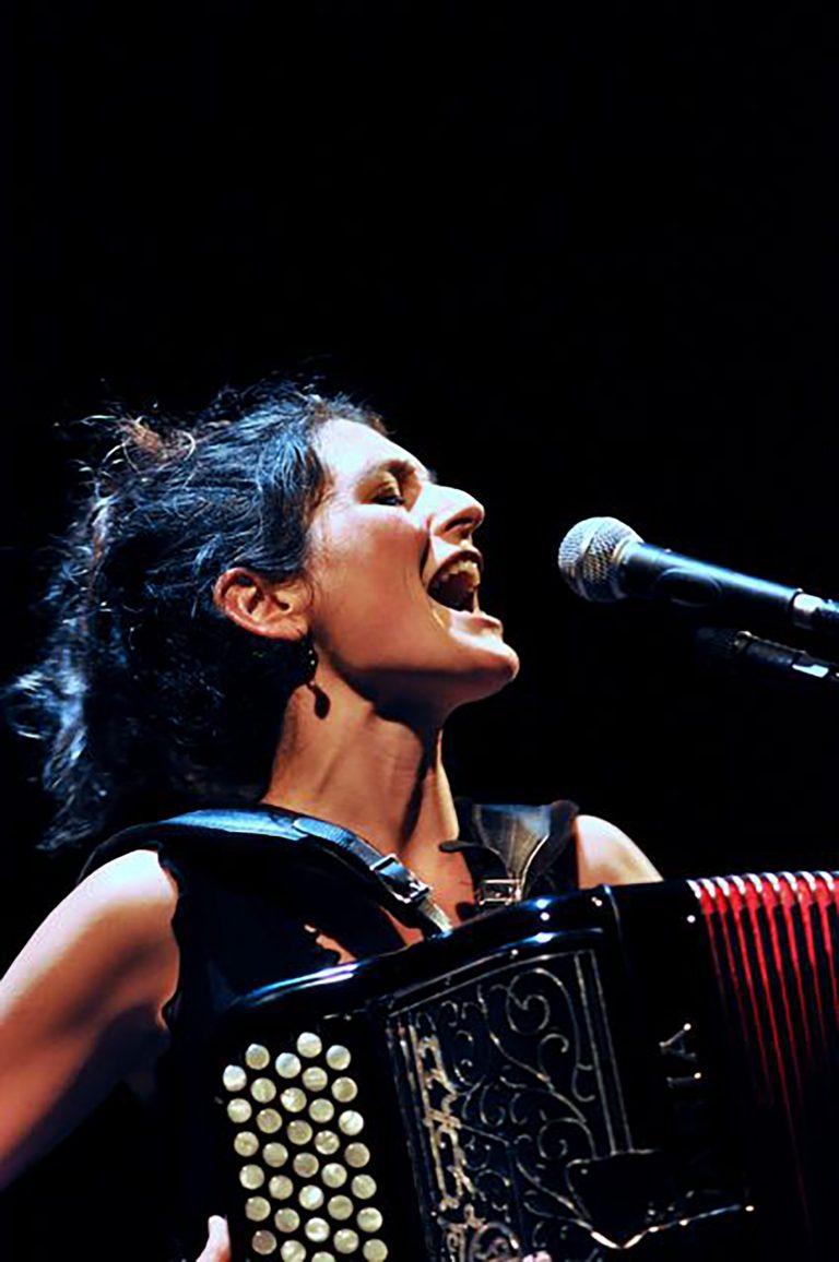 Chloé Lacan en train de chantant sur scène avec son accordéon
